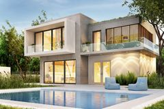 Evening view of a modern home with lighting and a swimming pool. Evening view of a modern home with lighting and a pool royalty free stock images
