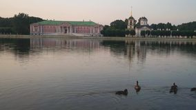 Evening view through the pond on the palace and church with bell tower in museum-estate Kuskovo, Moscow. stock footage