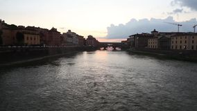 Ponte Vecchio in Florence Italy at sunset. Evening view of Ponte Vecchio old bridge over the Arno river from Ponte alle Grazie at colorful sunset. Famous stock footage