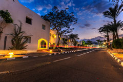 Evening view for road in illumination, white apartments, palm trees Stock Images