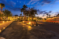 Evening view for road in illumination, white apartments, palm trees Stock Photo