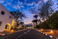 Evening view for road in illumination, white apartments, palm trees Royalty Free Stock Photo