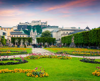Evening view of Salzburg Cathedral and old historic Fortress Hoh. Ensalzburg from Mirabell Garden. Colorful sunset in Austria, Europe. Artistic style post Royalty Free Stock Photo