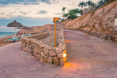 Evening view for a small road on beach in illumination Stock Photos