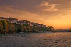 Evening view of a small town on rock cliff at sunset. Panoramic evening view of a small town on rock cliff at sunset in sozopol, bulgaria Royalty Free Stock Photo