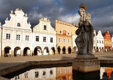 Evening view of Telc or Teltsch town square. Building mirroring in public fountain with statue of st. Margaret, Czech republic. World heritage site by unesco Stock Photos