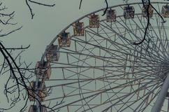 Evening view to ferris wheel surrounded by tree bushes Stock Image
