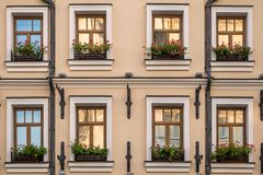 Two rows of windows with flowers. Evening view of Two rows of windows with flowers stock images