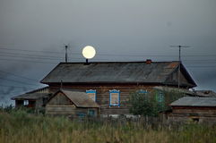 Evening in the village. Moon over a wooden house in the Russian village Stock Photography