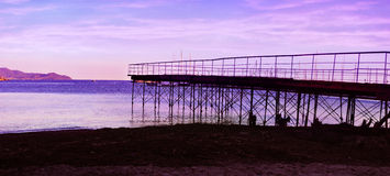 Evening violet sky with silhouettes of pier Stock Photo