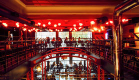 Evening visitors sitting inside the red light space of modern city bar Royalty Free Stock Image