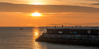 Evening walk on breakwater. Joggers and walkers are silhouetted by a beautiful sunset as they enjoy an evening on a breakwater.in Victoria British Columbia Stock Photo