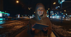 Evening walk in the city with tablet computer. Steadicam shot of a young smiling woman walking in the evening city in autumn or spring and using touch pad stock footage
