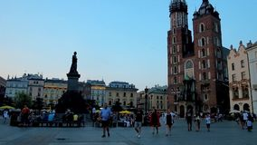 Evening walk in Krakow center, Poland. KRAKOW, POLAND - JUNE 11, 2018: The twilight sky over the Main Market Square and its main landmarks - St Mary`s Basilica stock video