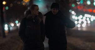Evening walk of two friends. Two women friends having a walk in cold winter evening. Blurred lights of moving cars in background stock video footage
