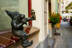 Evening walk in Wroclaw, Silesia, Poland. Wroclaw, Silesia, Poland - July 25, 2017: Miniature bronze figure of a gnome who eats ice cream on the windowsill of an Royalty Free Stock Image