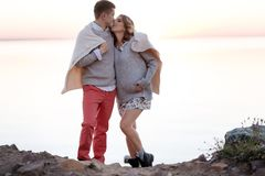 Young family expecting a baby walking together covered with a plaid royalty free stock photos