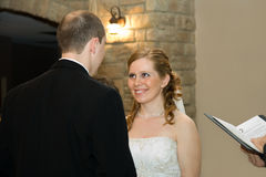 Evening Wedding Ceremony. Bride and groom exchanging smiling at one another during the wedding ceremony stock photos