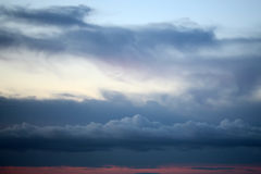 Evening white blue and red cloudy sky Royalty Free Stock Photos