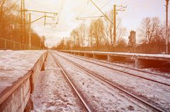 Evening winter landscape with the railway station. Snow-covered railway platform under the sun light at sunset. A place where peo Royalty Free Stock Photos