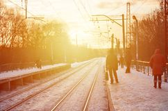 Evening winter landscape with the railway station. Snow-covered railway platform under the sun light at sunset. A place where peo Royalty Free Stock Image