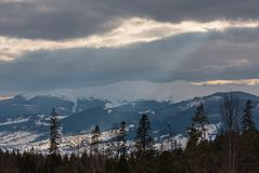 Evening winter mountain ridge and sun rays from cloudy sky royalty free stock images