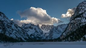 Evening in the winter mountain valley. Alpine slope illuminated by reflected sunlight Royalty Free Stock Images