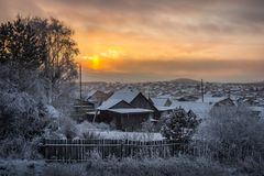 Evening winter sunset over suburban houses on horizont. Winter. Landscape with snowy village Royalty Free Stock Image