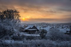Evening winter sunset over suburban houses on horizont. Winter. Landscape with snowy village Stock Photos