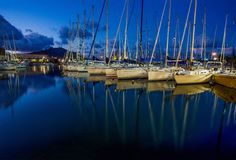 Evening Yachts in harbor  of Palermo. Evening -    Yachts docked in the port of Palermo. City  lights. Blue  skay and water stock image