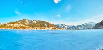 Evening on Zeller see lake, Zell am See, Austria. When the sun hides behind the mountains the snow crust surface of Zeller see lake becomes bright blue royalty free stock photography