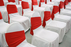 Event chairs. With white and red decoration lined up in row Royalty Free Stock Photography
