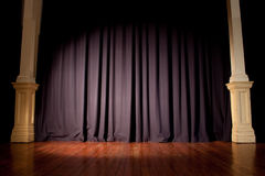 Event Expectation. Blue event curtain with spotlight, supported by two pillars. Wooden floor. Loads of copy space stock image