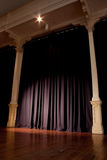 Event Expectation Vertical. Blue event curtain with spotlight, supported by two pillars. Wooden floor. Loads of copy space royalty free stock images