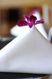 Event Flowers. A single flower in a folded napkin on table at reception Stock Photography