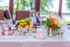 Event hall arrangements. Table arrangements and decoration details with wooden letters an miniature wooden houses Stock Photo