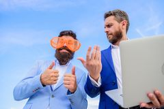 Event management industry. Unprofessional behaviour. Businessman with laptop serious while business partner ridiculous. Glasses looks funny. How stop play stock photo
