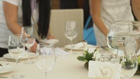 The event managers are engaged in seating of guests in a restaurant. Two girls are counting the invitations before celebrating a feast. Wineglasses, plates and stock video