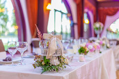 Event table arrangements. With different white and pink flowers green leaves and white miniature bird cage Stock Images