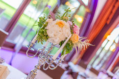 Event table arrangements. Silver candlestick arrangements with different white and orange flowers and white candles Stock Images