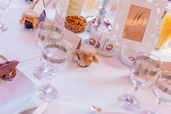 Event table arrangements. Table arrangements with small jam jar gifts and amazing crystal glasses with golden details Stock Image