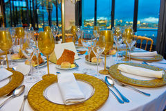 Event Tables Set, Dinner Party with Ocean view, Lecture Banquet Decoration. Wedding, party or business event tables decoration in white and golden tones. Silvery Royalty Free Stock Image