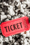 Event ticket lying on pile of popcorn. Show scene of a retro red ticket lying on pile of popcorn. Event entry Stock Photo