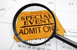 Event ticket search. Magnifying glass and Special Event ticket stub on a calendar Stock Images