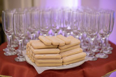 Table arrangement featuring empty flutes for champagne and lady finger sponge biscuits Royalty Free Stock Photography