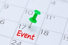 Event written on a calendar with a green push pin to remind you royalty free stock photo