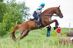 Eventer en caballo es salto la cerca a campo través Fotografía de archivo libre de regalías