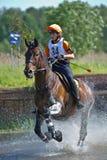 Eventer en caballo es supera el salto de agua Fotografía de archivo