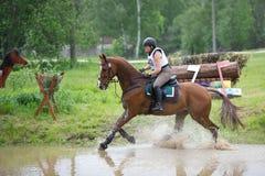Eventer en caballo es supera el salto de agua Fotos de archivo