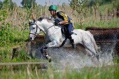 Eventer en caballo es supera el salto de agua Imagenes de archivo